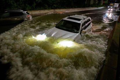 Un vehículo atraviesa una calle inundada en Brooklyn.