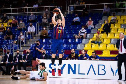 Kuric lanza un triple, con Bassas en el suelo, en el partido Barça-Joventut.