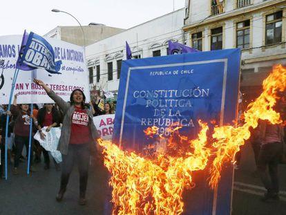Manifestantes queman una imagen de la Constitución de Chile.