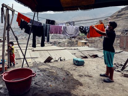 Habitantes del barrio Los Jazmines, en Lima (Perú), extienden sus ropas recién lavadas.
