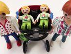 Unos padres múltiples pasean a sus bebés en su carrito gemelar, de Playmobil.