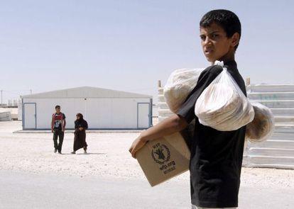 Un refugiado sirio carga con provisiones de alimento en el campo de refugiados sirios de Zatari.