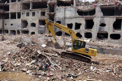 Una grúa limpia los escombros de la fábrica textil derrumbada en la localidad de Dacca.