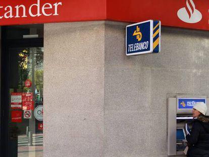 Una mujer retira dinero de un cajero automático en una oficina de Banco Santander.