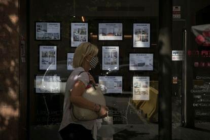 Una mujer pasa frente a una inmobiliaria en Barcelona.