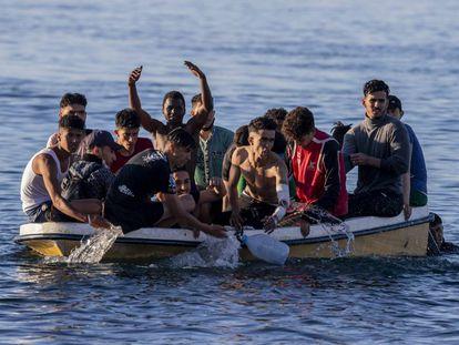 Un grupo de jóvenes cruzan en barca la frontera de Marruecos y España, este miércoles.