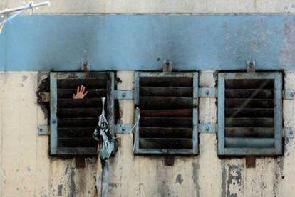 Un interno pide ayuda desde el interior de su celda en la cárcel de San Miguel.