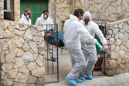 Trabajadores de una empresa funeraria de Palma trasladan un cadáver equipados con monos y mascarillas.