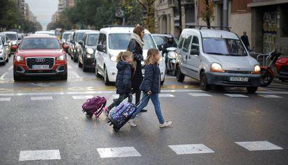 Varias personas cruzan un paso de peatones en la transitada calle Aragó de Barcelona.