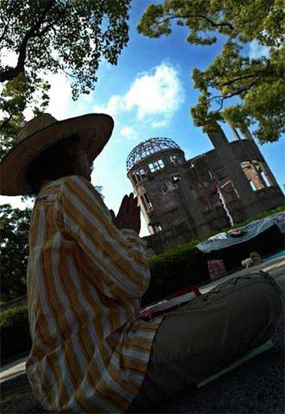 """Una mujer reza frente al antiguo Salón Provincial de Exposiciones, declarado Patrimonio de la Humanidad por la Unesco en 1996 como """"herencia que transmite a los hombres su pasado histórico""""."""
