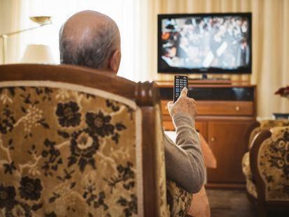 Un hombre mayor viendo la televisión.