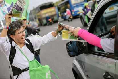 Claudia López reparte periódicos en las calles de Bogotá.