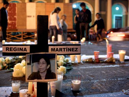 A photograph of slain journalist Regina Martinez hangs on a cross during a vigil in her honor outside the municipal offices in Xalapa, Mexico, late Sunday April 29, 2012. The Mexican government's human rights commission said Sunday that it will investigate the apparent slaying of a correspondent for Proceso newsmagazine who often wrote about drug trafficking. Police found the body of Martinez on Saturday inside the bathroom of her home in the Veracruz state capital, Xalapa. (AP Photo/Felix Marquez)
