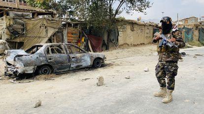 Un militar frente a un coche destruido por EE UU en Kabul (Afganistán).