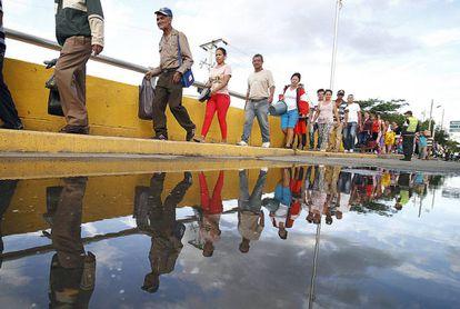 Venezolanos cruzan el puente Simón Bolívar después de hacer compras en Colombia.