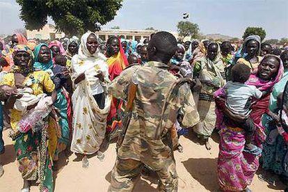 Un policía sudanés trata de mantener a raya a un grupo de mujeres durante un reparto de alimentos en un campo de desplazados de Darfur.