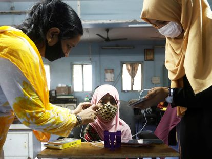 Varias profesoras ayudan a una estudiante a prepararse antes del inicio de una lección a través de un teléfono móvil, dentro de una biblioteca de educación móvil digital, iniciada para proporcionar dispositivos a los niños que no tienen acceso a ellos para recibir educación en Mumbai, India.