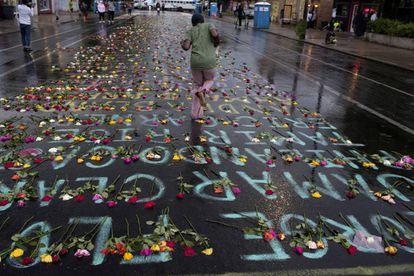 Flores y los nombres de las víctimas de la violencia policial, en la calle de Minneapolis en la que murió George Floyd a manos de la policía el pasado junio.