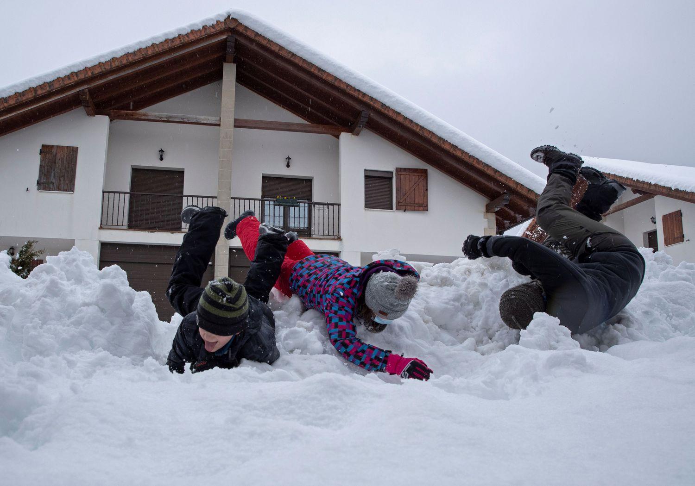 Tres niños se divierten en la nieve caída en Espinal (Navarra).