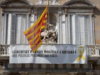 Fachada del Palau de la Generalitat de donde cuelga, junto a la bandera catalana, un cartel y un lazo amarillo reivindicando la libertad de los políticos encarcelados.