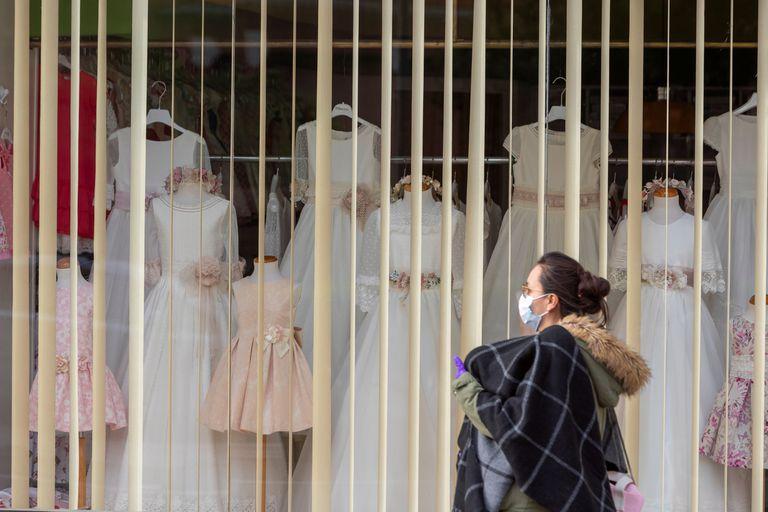 Una mujer pasa delante de una tienda cerrada en Zaragoza.