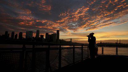 Una mujer fotografía el atardecer en Seattle (Estados Unidos), ejemplo de ciudad global gracias al empuje de las grandes empresas tecnológicas.