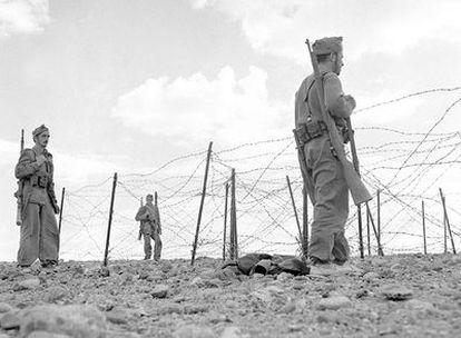 Soldados españoles de infantería patrullan frente a la valla defensiva de una ciudad del Sáhara, probablemente El Aaiún, en los años 1957-1958.