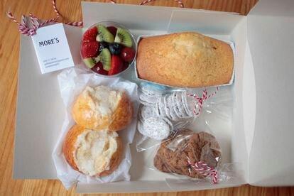 Desayuno artesano de More's a domicilio con bizcocho, suizos, fruta y galletas.