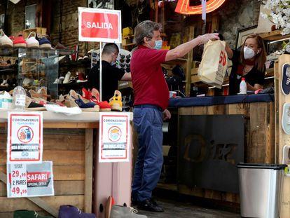 Un cliente compra en una tienda del centro de Madrid este lunes, tras la reapertura del pequeño comercio.