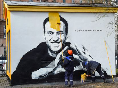 Un trabajador pinta sobre un grafiti con el retrato del opositor ruso Alexéi Navalni, el 28 de abril en San Petersburgo.