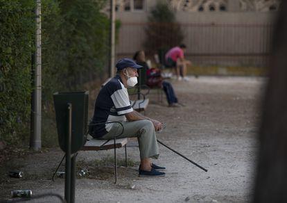Un hombre descansa en un banco de Puente de Vallecas, una de las zonas mas afectadas por el aumento de contagios de la covid-19.
