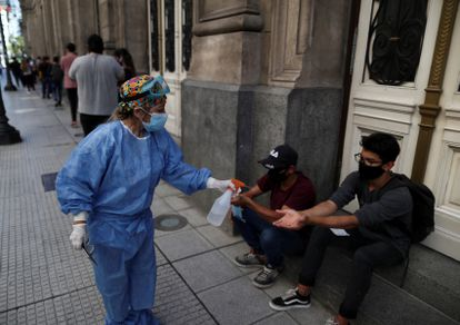 A health worker offers antibacterial gel to a couple of young people outside the Teatro de Colón in Buenos Aires.