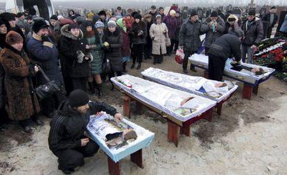 Familiares y amigos en los funerales de Nikolay y Lyubob Bobilev, su hija Marina y su nieto de tres años Vyacheslav, muertos en Mariúpol.