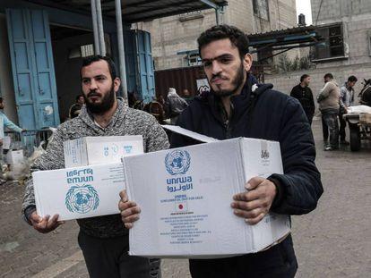 Refugiados palestinos recogen paquetes con ayuda de la ONU en Jan Yunis (Gaza).