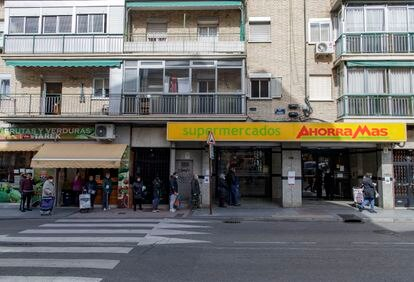 Varias personas con mascarilla hacen cola en un supermercado Ahorra Más en Alcorcón, Madrid.