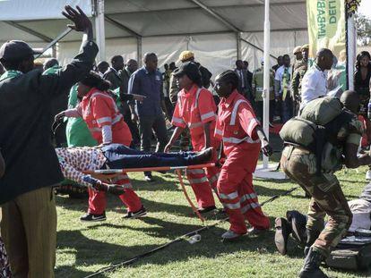 Efectivos de emergencias trasladan a un herido durante un mitin del presidente Emmerson Mnangagwa, este sábado en Zimbabue.