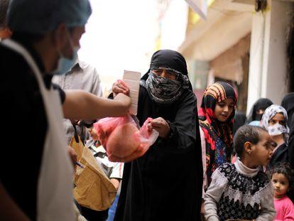 Una mujer recibe una ración de comida este julio en Saná, en Yemen.