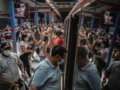 Decenas de personas entran a un vagón de la estación de Príncipe de Pío de Metro de Madrid.
