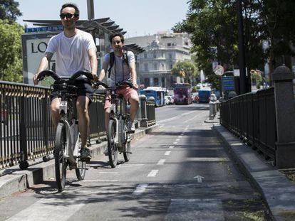 Dos ciclistas circulan en Bicimad por el carril bici de la calle Alcalá.