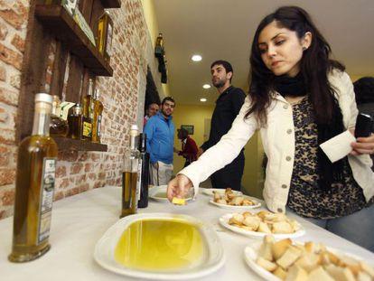 Una mujer prueba aceite de oliva con pan durante su visita a la primera Oleoteca Internacional dedicada al aceite de oliva virgen, en Santa Cruz del Valle (Ávila)