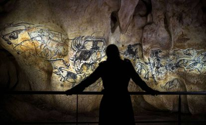 A person contemplates the reproduction of the paintings in the Chauvet cave (France).