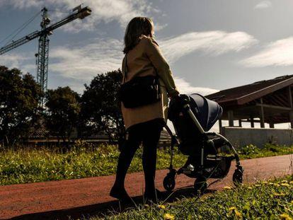 Una mujer pasea junto a su bebé frente a varios edificios en construcción.