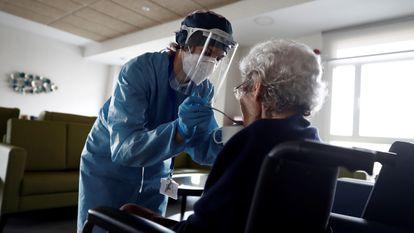 Una cuidadora ayuda a comer a una anciana en una residencia del barrio madrileño de Villaverde, en Madrid, en pasado abril.