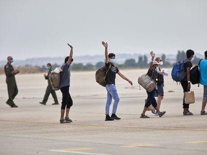 Un grupo de jóvenes afganos saludan, antes de subir a un avión estadounidense para ser trasladados a Alemania, en la base aérea de Torrejón de Ardoz, el 24 de agosto de 2021, en Madrid.