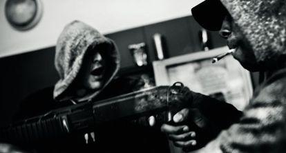 Dos tipos encañonando un arma en el portal de un edificio en octubre de 2012.
