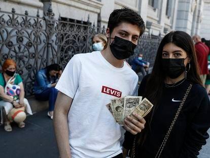 Mario Rodríguez, de 18 años, junto a su hermana Alba, de 23, esperan para cambiar las pesetas de su abuela en el Banco de España.