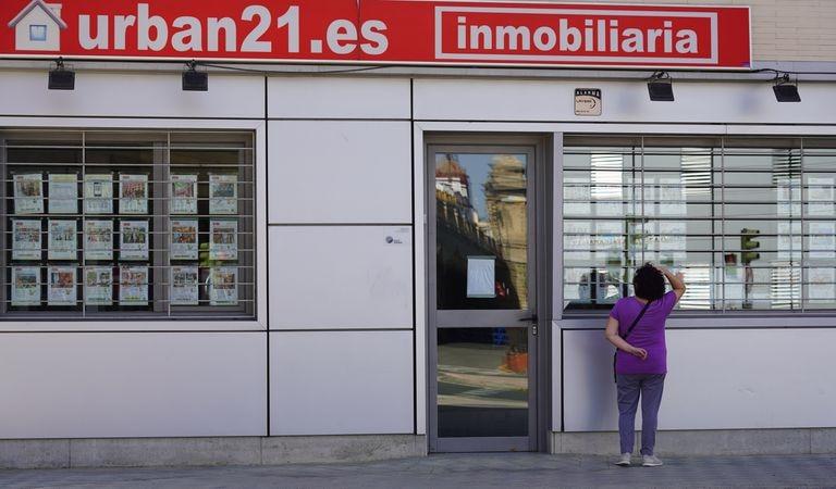 Una mujer mira el escaparate de una inmobiliaria en Sevilla, el pasado 4 de mayo.