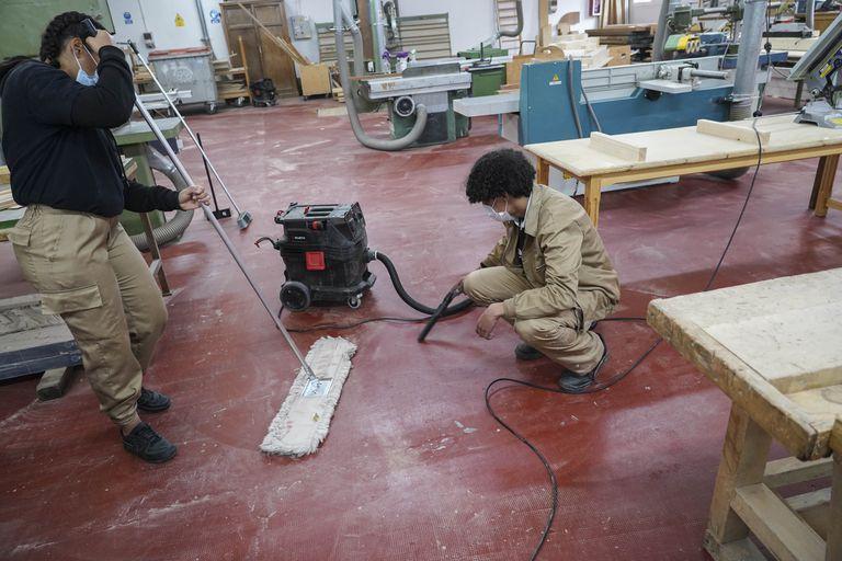 Daniela, dominicana de 17 años, limpia el taller de carpintería de Puerta Bonita junto a un compañero argelino.