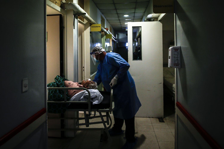 Un camillero realiza el traslado de una mujer con la covid-19 en una unidad de terapia intensiva, en Buenos Aires.