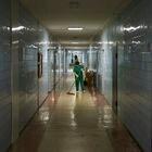 El equipo de limpieza, con bata verde y guantes amarillos, es el único que salen al pasillo en el hospital de Svitlodars'k.